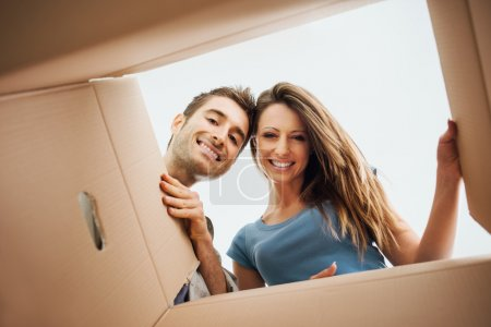 Photo for Smiling young couple opening a carton box and looking inside, relocation and unpacking concept - Royalty Free Image