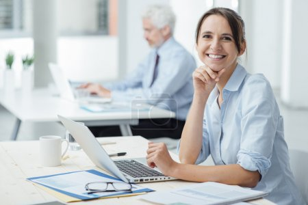 Photo for Smiling young business woman sitting at office desk and working with a laptop, she is looking at camera - Royalty Free Image