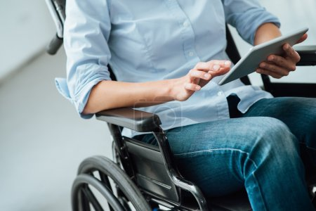 Woman in wheelchair using a tablet