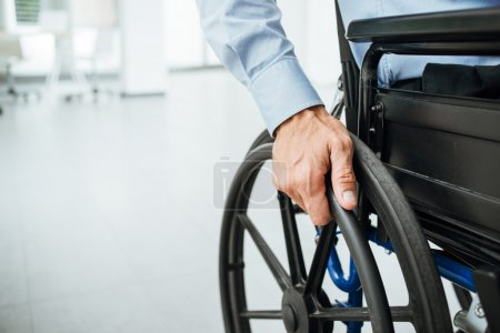 Photo for Businessman in wheelchair, hand on wheel close up, office interior on background - Royalty Free Image