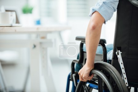 Photo pour Woman in wheelchair next to an office desk, hand close up, unrecognizable person - image libre de droit