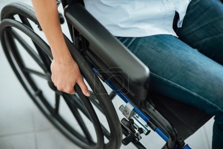 Photo pour Woman in wheelchair hand on wheel close up, disability and handicap concept - image libre de droit