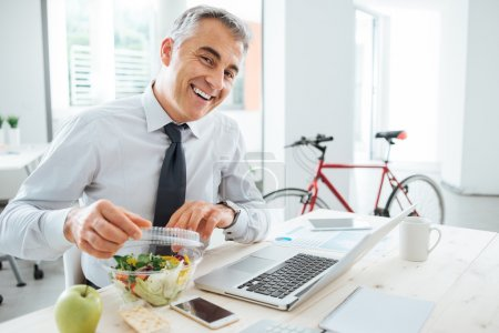 Photo for Happy businessman opening his salad pack and having a lunch break at office desk - Royalty Free Image
