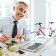 Happy businessman opening his salad pack and havin...