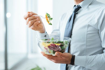 Businessman having a vegetables salad for lunch, h...