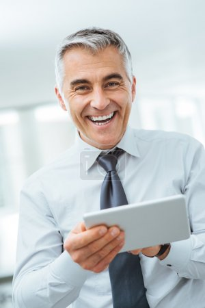 Smiling businessman using a digital tablet