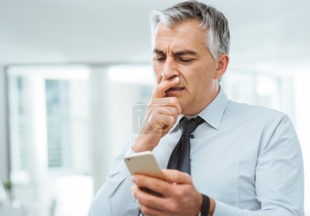 Confused businessman using a smart phone