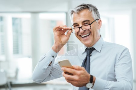 Photo for Smiling businessman with eyesight problems, he is adjusting his glasses and reading something on his mobile phone - Royalty Free Image
