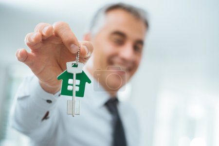 Photo for Confident real estate agent holding your new house keys and smiling at camera - Royalty Free Image