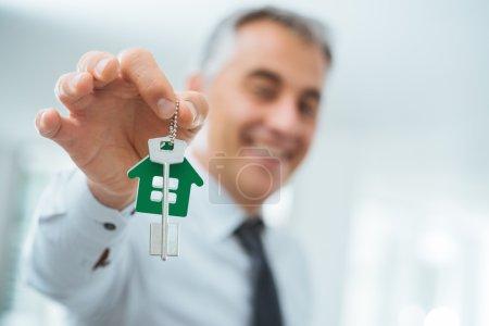 Photo pour Agent immobilier confiant tenant vos nouvelles clés de la maison et souriant à la caméra - image libre de droit