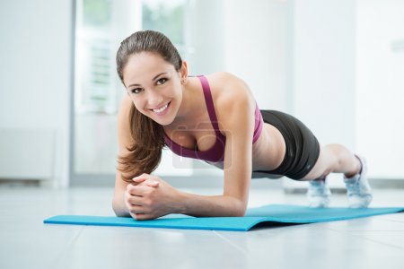 Photo for Smiling woman exercising at the gym on a mat, fitness and workout concept - Royalty Free Image