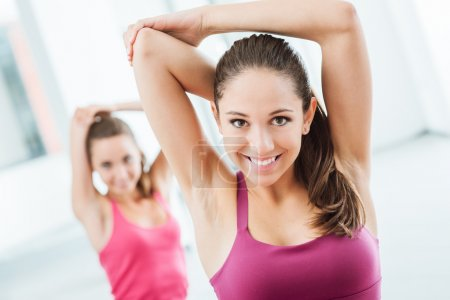 Girls doing stretching exercises at the gym