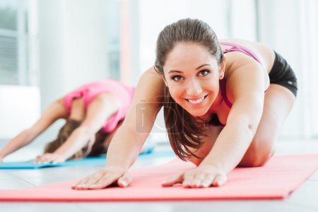 Photo for Girls at the gym doing stretching exercises on a mat, one is smiling at camera - Royalty Free Image