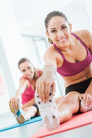 Photo pour Sourire des jeunes femmes à la salle de gym faire un exercice d'étirement pour les jambes sur une natte, le fitness et la notion de santé - image libre de droit