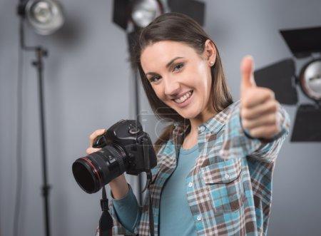 Photo pour Jeune photographe femme posant dans son studio professionnel, tenant un appareil photo numérique avec des appareils d'éclairage sur fond - image libre de droit