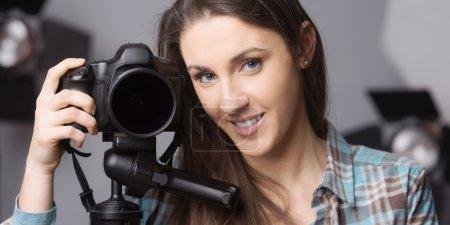Photo pour Jeune femme photographe posant avec une caméra numérique sur trépied et appareils d'éclairage sur fond - image libre de droit