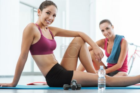 Beautiful young women at the gym sitting on a mat ...