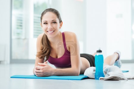 Photo for Smiling young woman relaxing after workout, she is resting belly down on a mat and looking at camera - Royalty Free Image