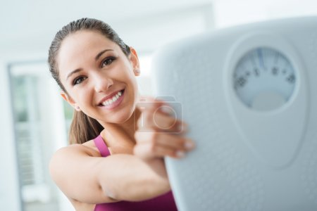 Photo for Happy young woman losing weight and showing a scale, dieting and fitness concept - Royalty Free Image