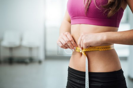 Slim woman measuring her thin waist