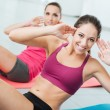 Smiling women exercising at gym on a mat and looki...