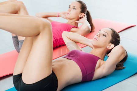 Young women doing abs workout at the gym