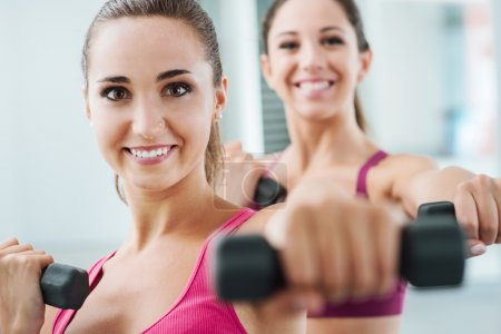 Cheerful women exercising at the gym