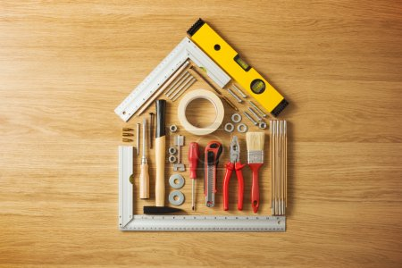 Photo for Conceptual house composed of DIY and construction tools on hardwood flooring, top view - Royalty Free Image