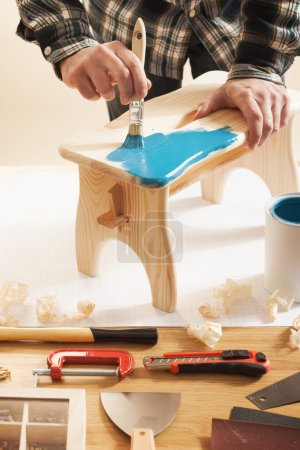 Craftsman varnishing and handmade stool