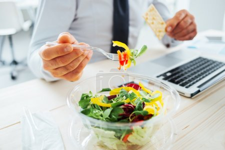 Photo for Businessman having a lunch break at desk, he is eating fresh salad and holding a cracker, unrecognizable person - Royalty Free Image