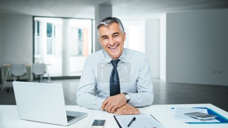 Photo for Confident handsome businessman sitting at office desk and smiling at camera - Royalty Free Image