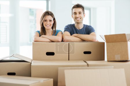 Photo for Young couple posing with arms crossed leaning on carton boxes and smiling at camera, home relocation concept - Royalty Free Image