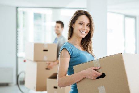 Photo pour Joyeux couple souriant emménageant dans une nouvelle maison et portant des boîtes en carton, concept de déménagement et de rénovation - image libre de droit