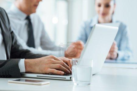 Photo pour Équipe entreprise entreprises travaillant au bureau, mains mâles taper sur un ordinateur portable sur le premier plan, mise au point sélective - image libre de droit