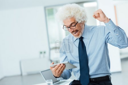 Cheerful successful businessman receiving good news