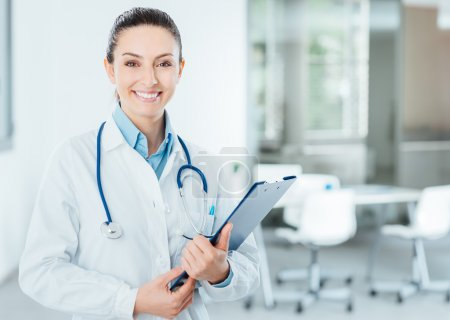 Photo for Smiling female doctor with lab coat in her office holding a clipboard with medical records, she is looking at camera - Royalty Free Image