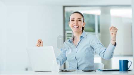 Photo for Successful cheerful businesswoman with fists raised sitting at office desk, achievement and satisfaction concept - Royalty Free Image