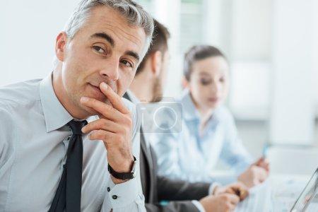 Photo pour Homme de confiance professionnel souriant à la caméra, de bureaux et d'affaires équipe travaillant sur le fond, mise au point sélective - image libre de droit