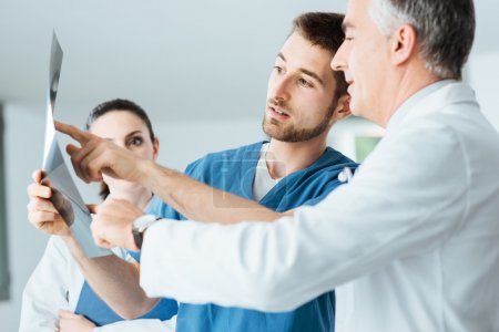 Photo for Professional medical team with doctors and surgeon examining patient's x-ray image, discussing and pointing - Royalty Free Image