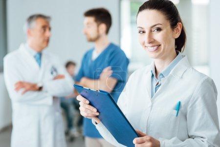 Photo pour Médecin professionnel souriant à la caméra et posant, personnel médical travaillant sur fond, mise au point sélective - image libre de droit