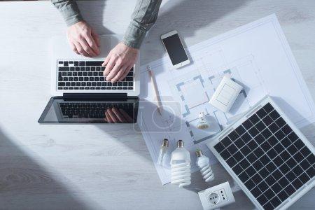 Foto de Hombre trabajando en su escritorio en un ordenador portátil con lámparas CFL de ahorro de energía, un panel solar y un proyecto de casa, vista superior - Imagen libre de derechos