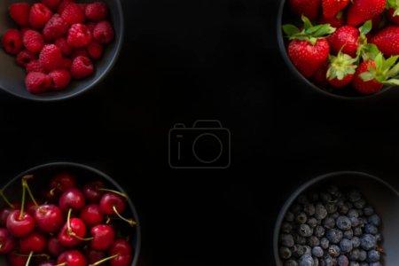 Photo pour Baies et cerises dans quatre bols, concept alimentaire créatif.Cerises fraîches, fraises, bleuets, framboises.Fruits de la forêt frais sur fond noir.Copier l'espace pour le texte. - image libre de droit