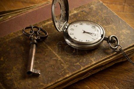 Foto de Reloj de bolsillo vintage, libro antiguo y una llave de latón en una superficie vintage - Imagen libre de derechos