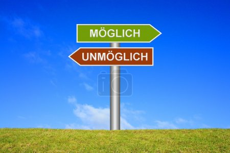 Signpost sign with blue sky and green grass showing impossible or possible in german language