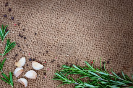 Fresh rosemary, garlic and spices on sackcloth background