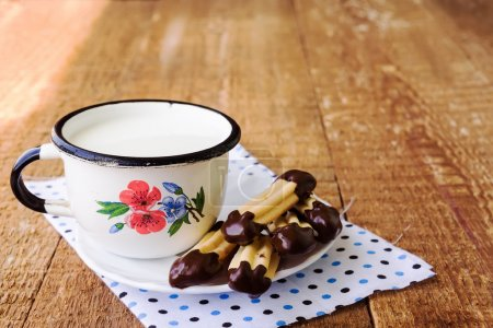 Homemade churros (finger biscuits) with mug of milk on wooden ta