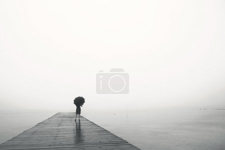 Woman with umbrella contemplates peacefully in fro...