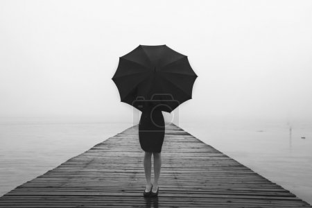 Photo for Elegant woman dressed in black hiding with umbrella in a misty landscape - Royalty Free Image