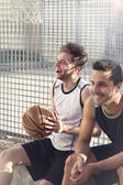 basketball players repose sitting in a urban place