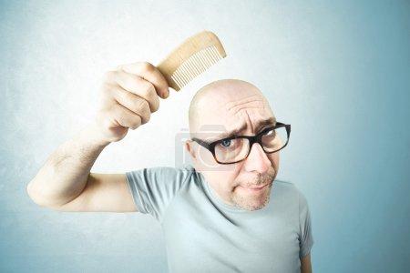Nostalgic man comb his bald head in the moring